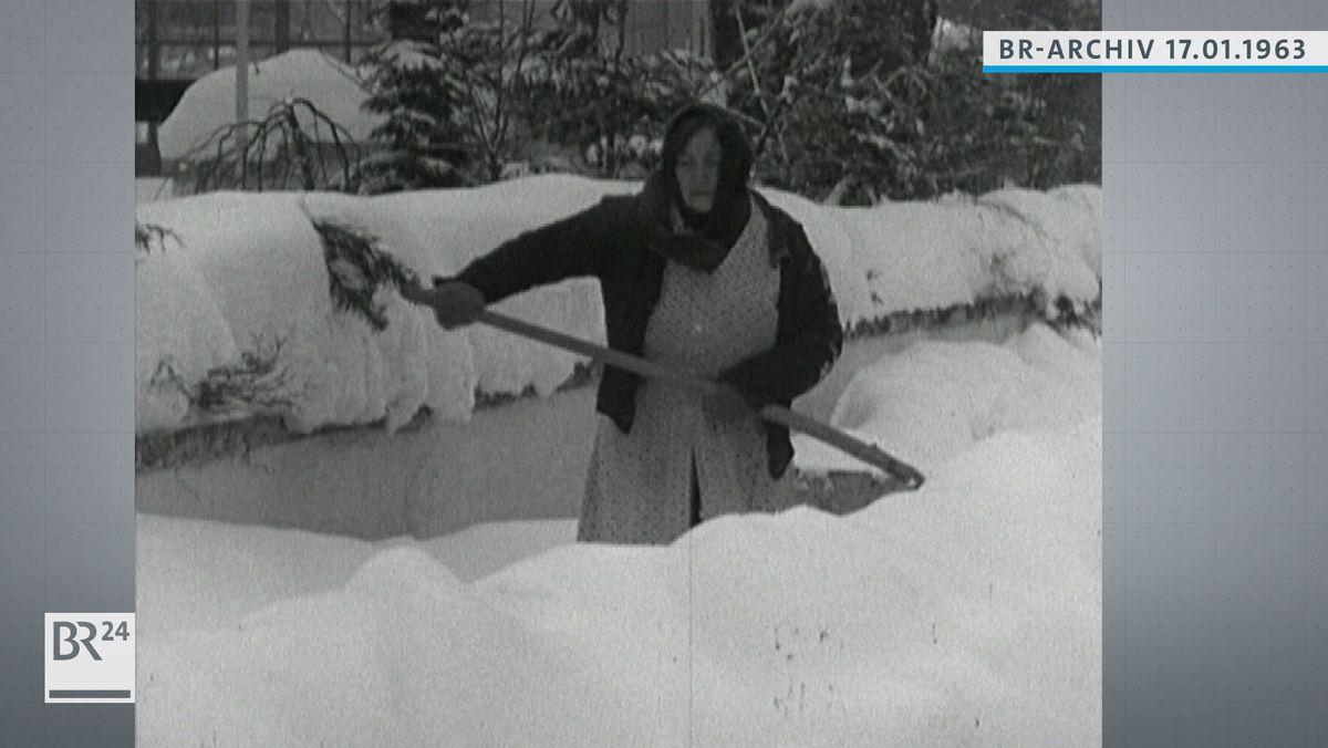 Frau beim Schneeräumen im knietiefen Schnee