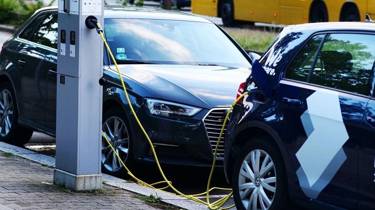 Zwei Elektroautos stehen an einer Ladesäule für E-Autos.