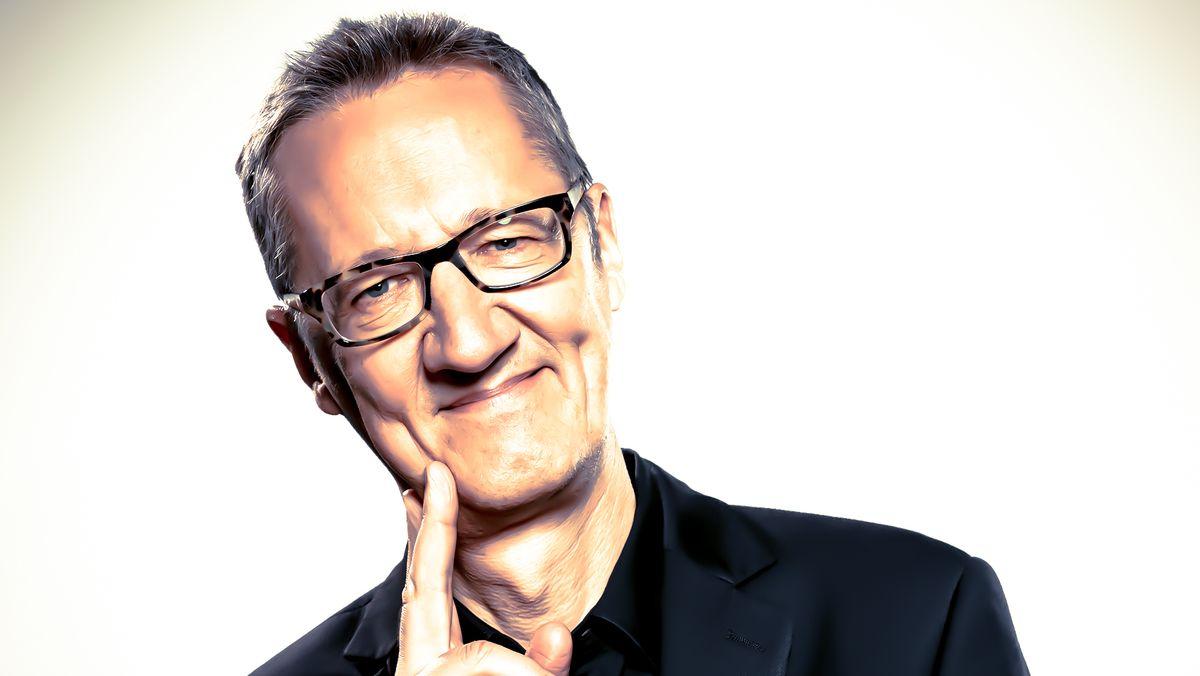 Porträt des Kabarettisten Holger Paetz in Denkerpose, mit Brille und verschmitztem Lächeln
