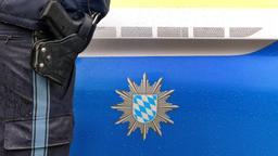 Polizist mit Handschellen und einer Pistole am Gürtel steht vor einem Streifenwagen | Bild:picture alliance/Karl-Josef Hildenbrand/dpa