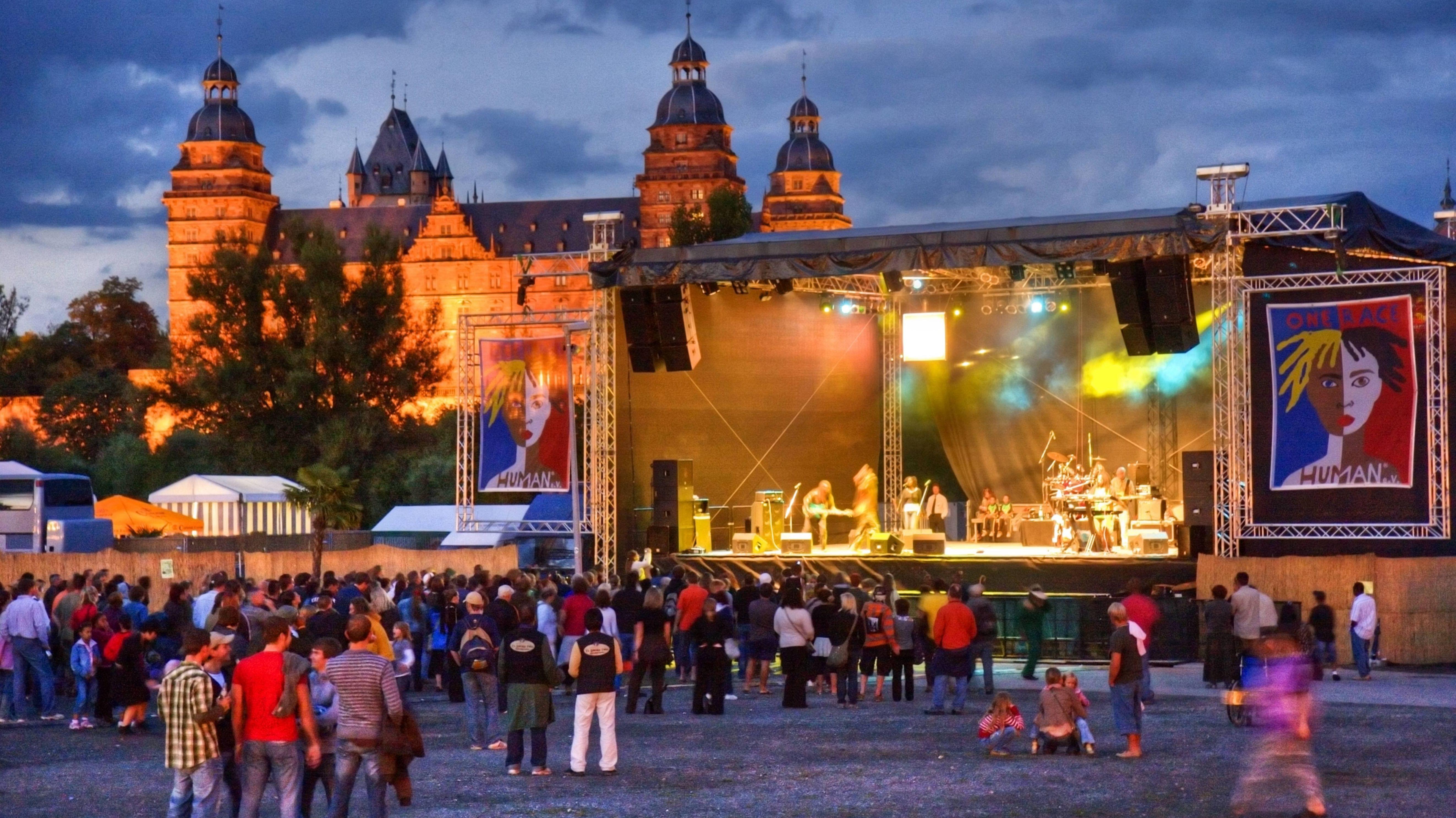 Die Hauptbühne des One Race...human-Festivals mit Band im Abendlicht. Dahinter ist das Aschaffenburger Schloss Johannisburg zu sehen.