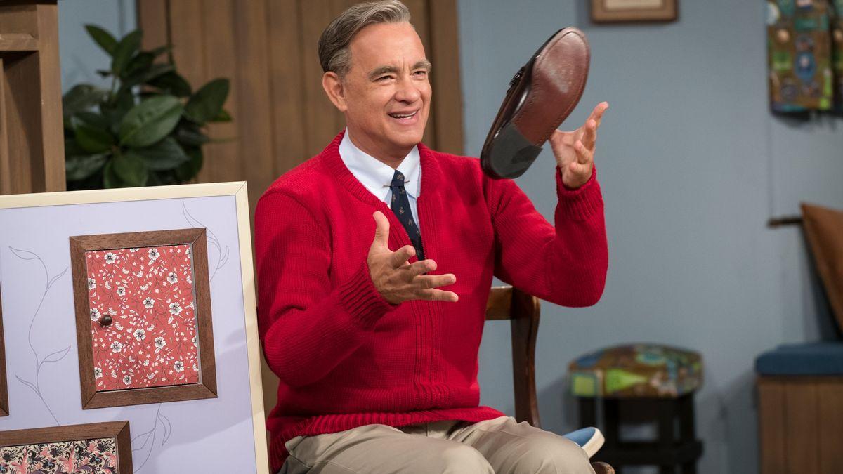 Fred Rogers sitzt in seiner typischen roten Strickjacke auf einem Stuhl und wirbelt einen Schuh durch die Luft
