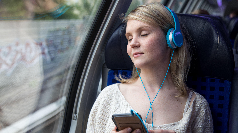 Junge Frau hört während der Zugfahrt mit ihrem Kopfhörer (Symbolbild)