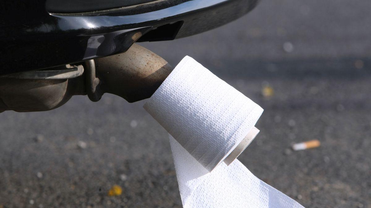 Eine Rolle Toilettenpapier an einem Auspuff eines Autos.