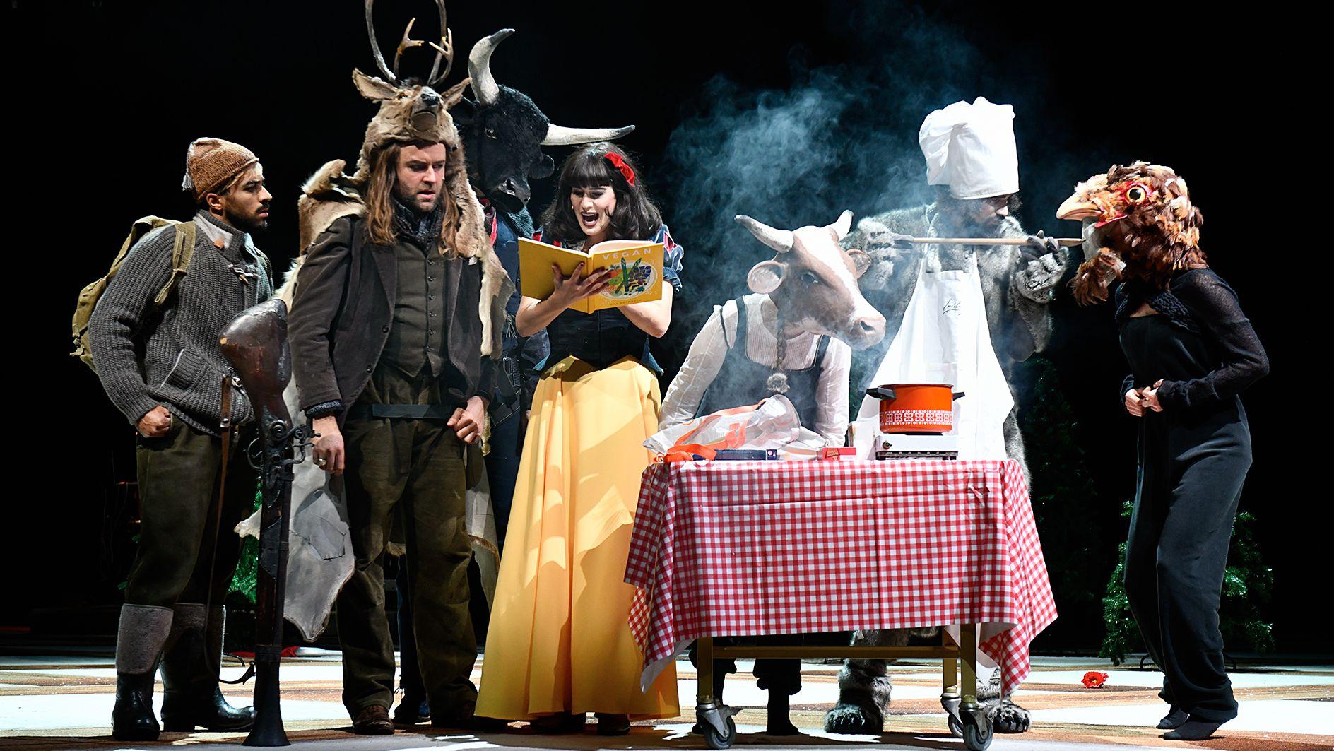 """Bild der Aufführung """"Schneewittchen"""" am Schauspiel Zürich. Es sind verschiedene Märchenfiguren zu sehen, darunter auch Schnewittchen selbst in gelbem Rock und roter Schleife im Haar."""