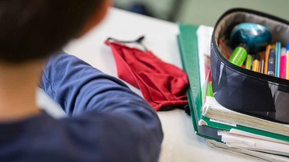 Schulkind am Tisch mit Unterrichtsunterlagen und Maske