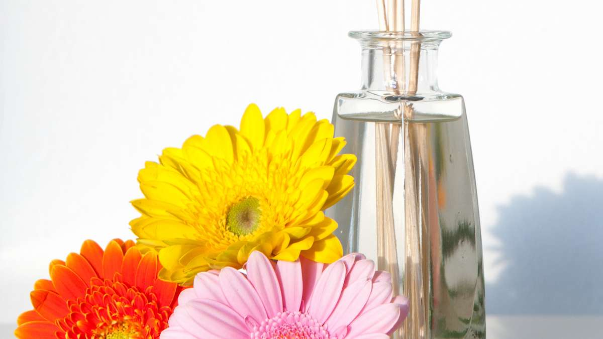 Eine Flasche mit Duftöl und Blüten