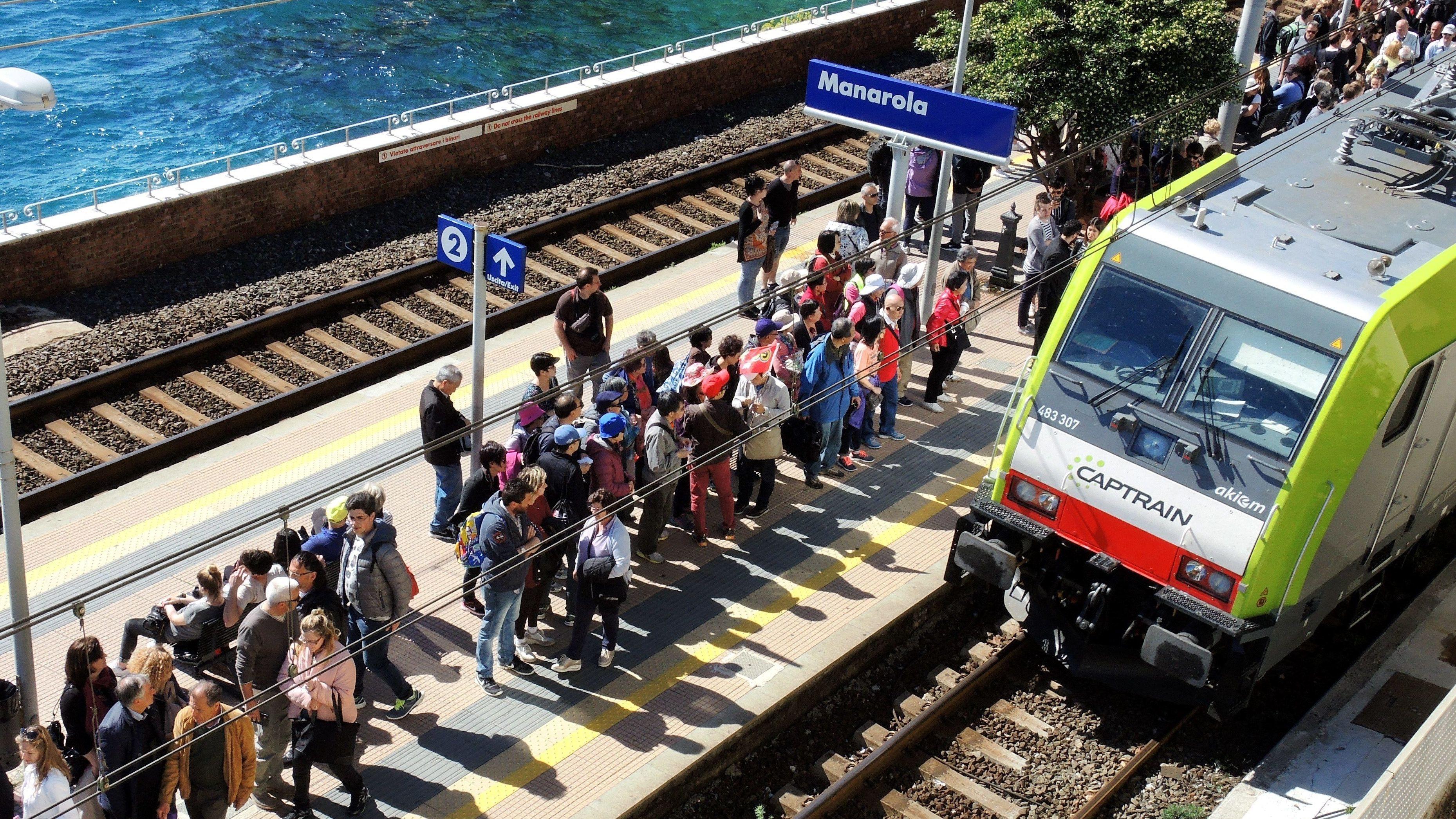 Touristen warten in Manarola auf einen Zug
