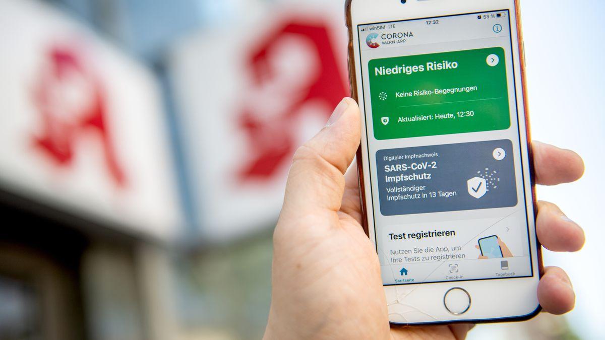 Der digitale Impfnachweis auf der Corona-Warn-App ist vor einem Apotheken-Logo auf einem Smartphone zu sehen.