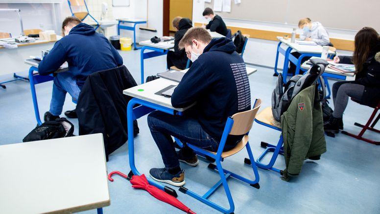 Schülerinnen und Schüler eines geteilten Kurses der Oberstufe sitzen in einem Klassenraum. | Bild:dpa-Bildfunk/Hauke-Christian Dittrich