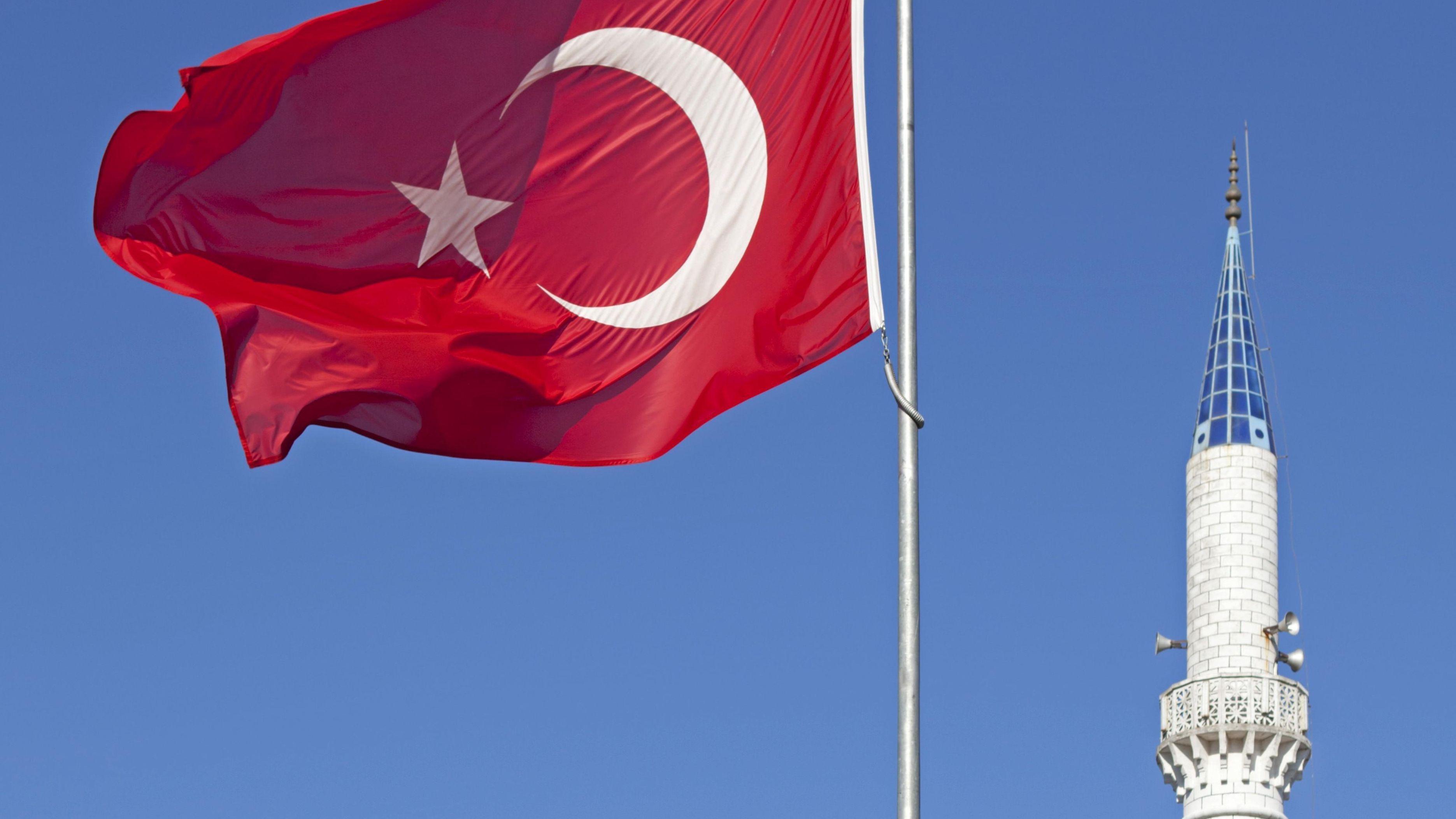 Türkische Flagge weht vor einem Minarett.