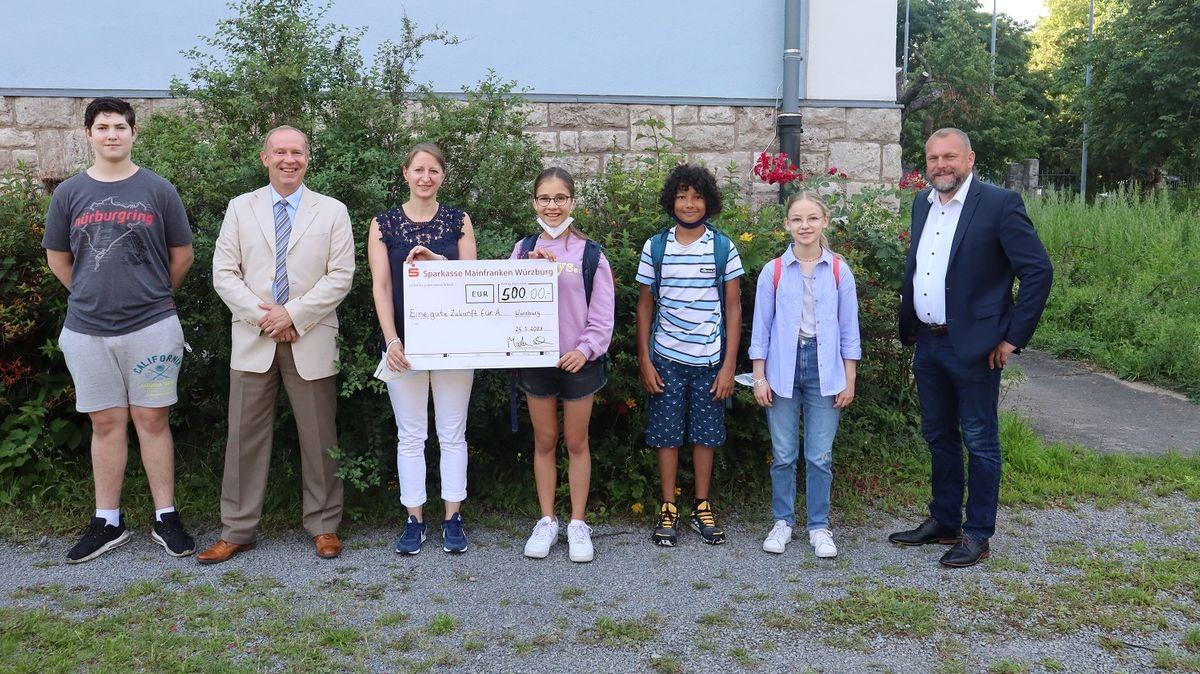 Schüler und Schulleiter des Matthias-Grünewald-Gymnasiums überreichen den Spendenscheck an das Landratsamt.