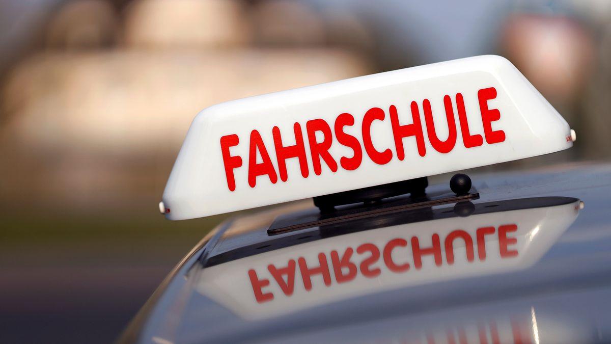 """Ein Schild mit dem Schriftzug """"Fahrschule"""" auf dem Dach eines Autos."""