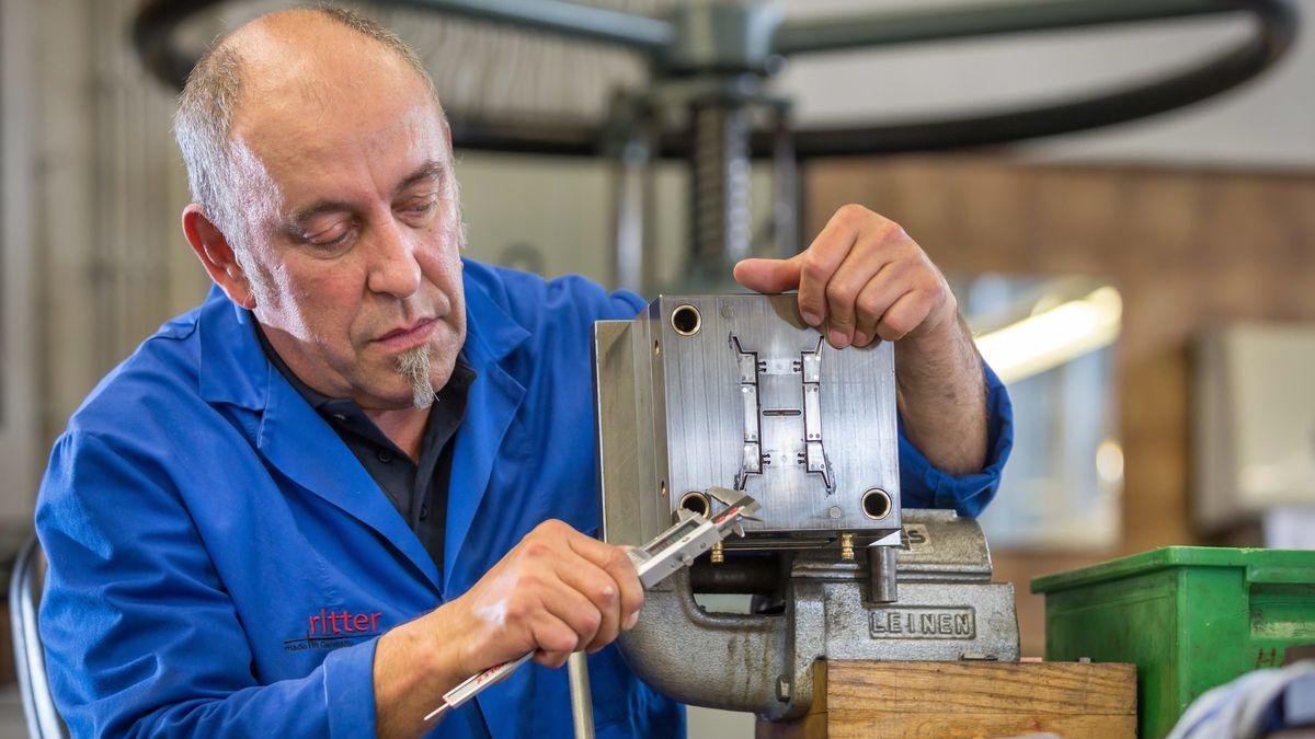 Ein Mitarbeiter vermisst in einer Werkzeugproduktion in eine Spritzgussform.