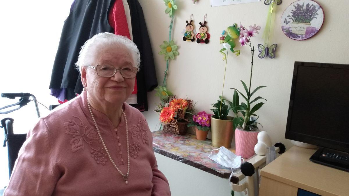 Katharina Eckert sitzt in ihrem Zimmer. Neben dem Fernseher stehen Blumen der Tochter.