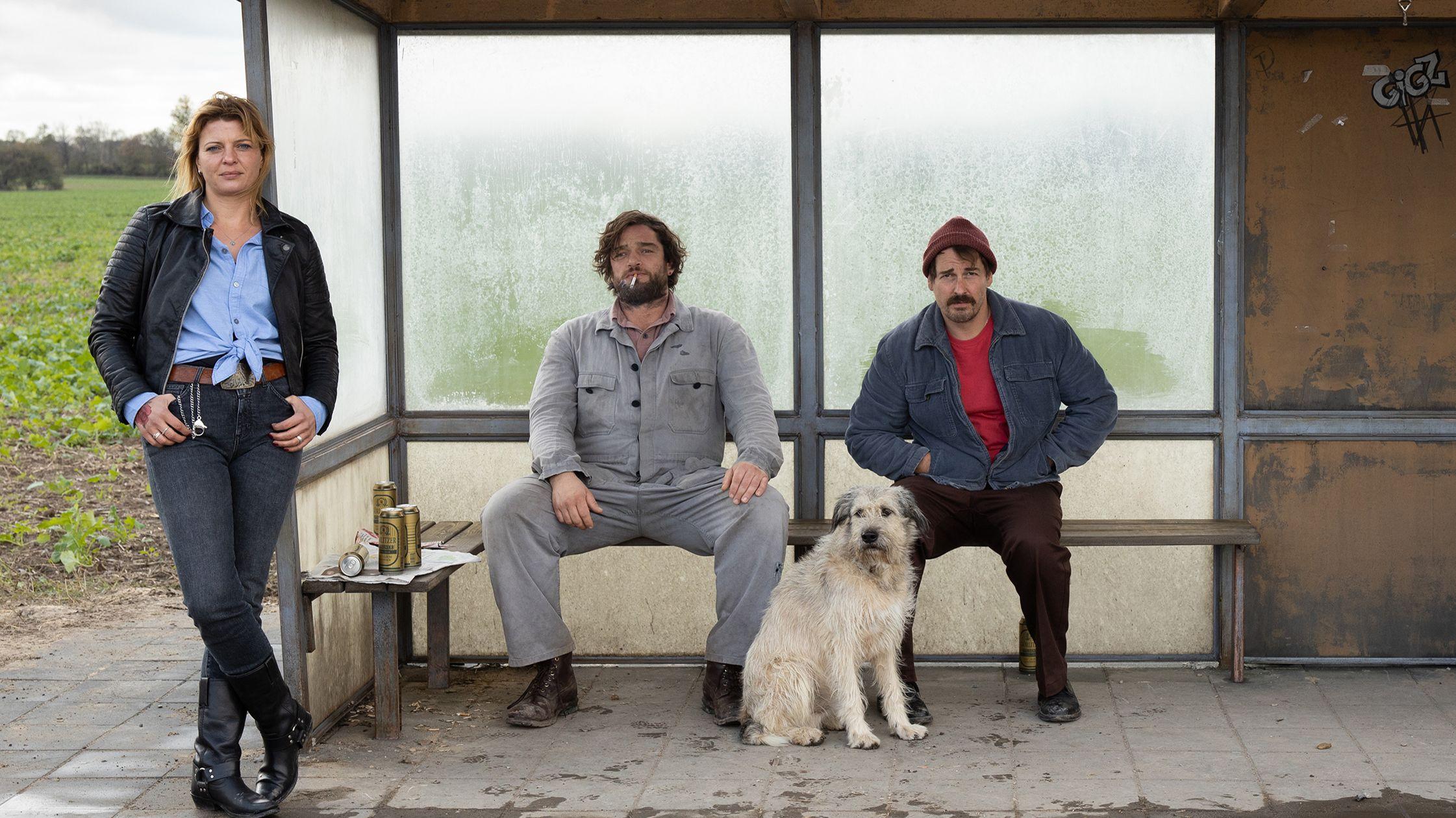 Eine Frau steht vor einer Bushaltestelle, in der zwei Männer mit einem wuscheligen Hund sitzen und missmutig vor sich hinstarren, mit Bierdosen neben sich und einer mit Glimmstängel zwischen den Lippen.