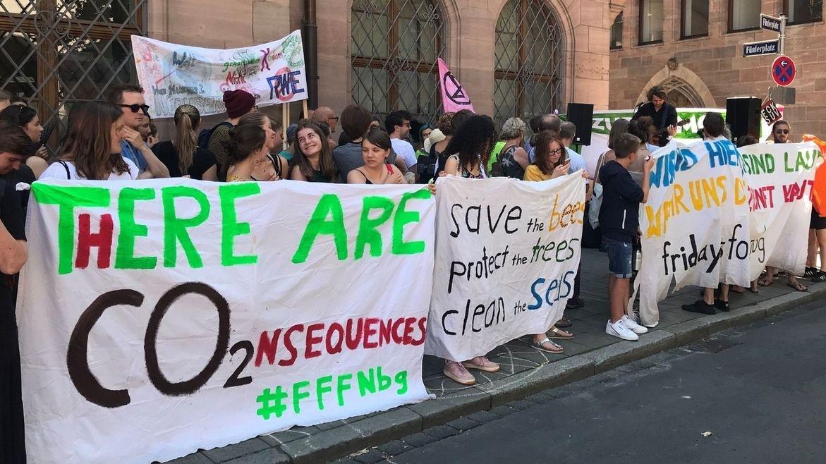 Junge Leute der Fridays for Future Bewegung demonstrieren in Nürnberg mit Transparenten, auf denen auf den Kohlendioxid-Ausstoß beim Verbrennen fossiler Rohstoffe hingewiesen