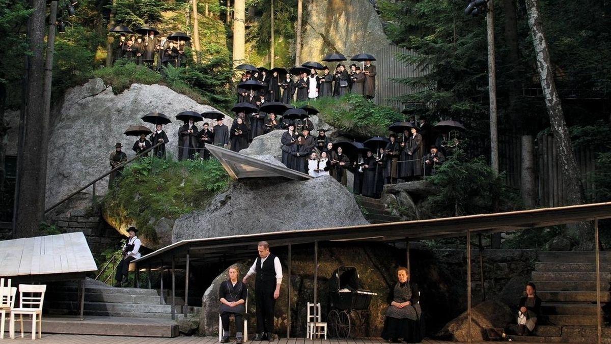 Schwarz gekleidete Schauspieler stehen auf der Freilichtbühne und halten schwarze Regenschirme in der Hand.