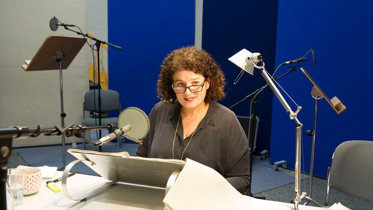 Dame in schwarzer Bluse mit dunklen Haaren und Brille in einem BR-Studio
