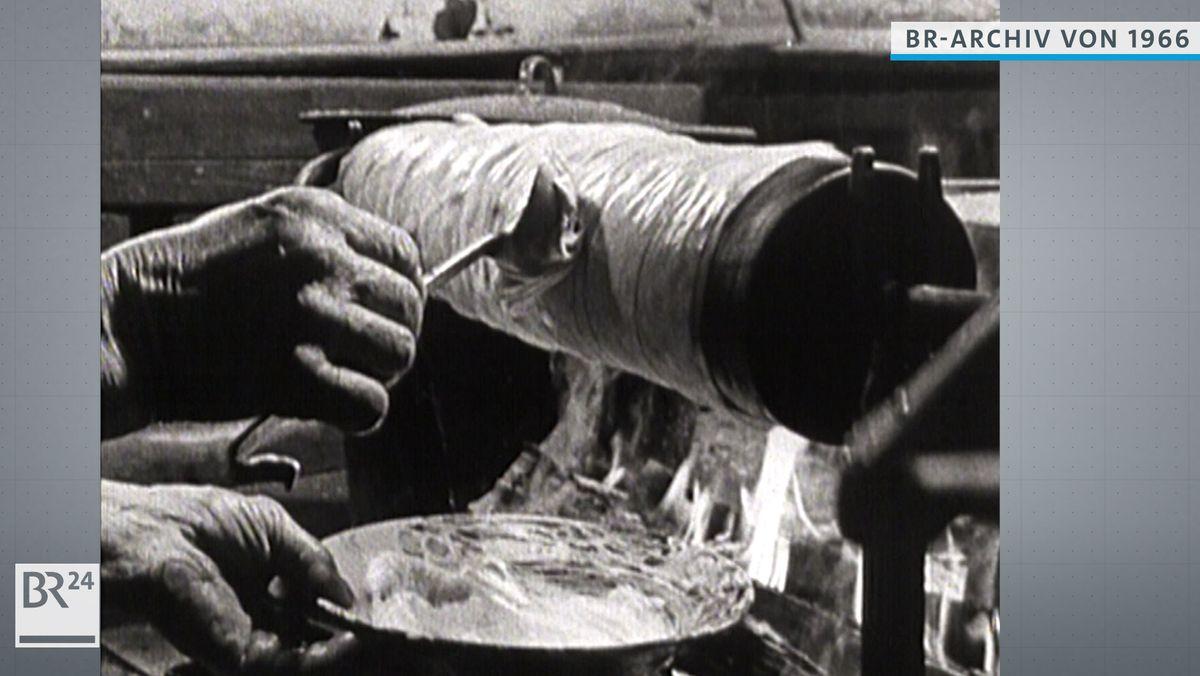 Der Teig wird auf den mit Pergamentpapier bespannten Prügel gestrichen
