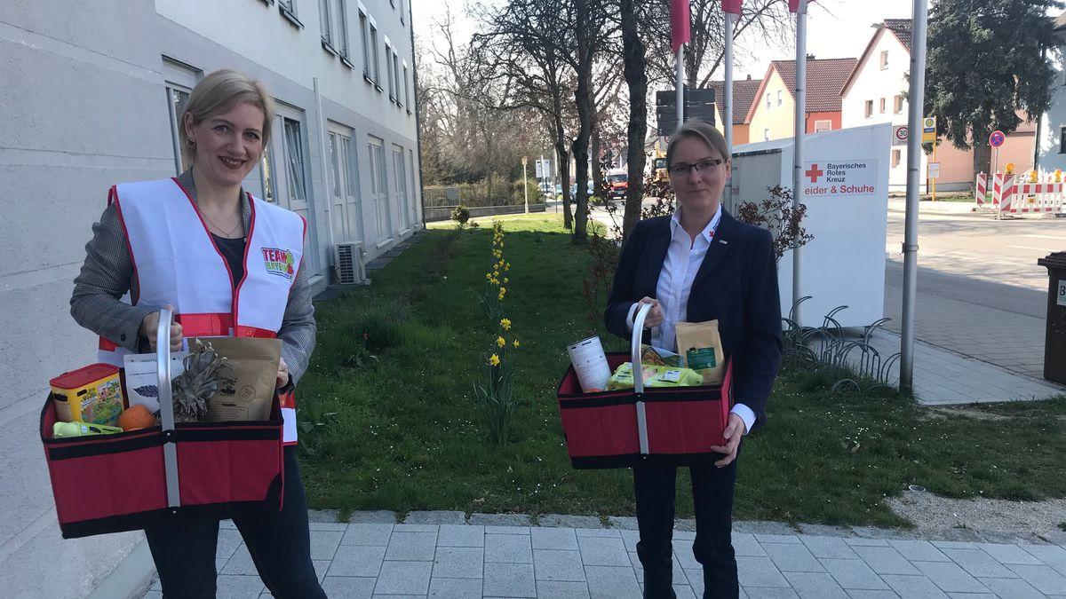 """Zwei freiwillige """"Team Bayern""""-Helferinnen bringen den bestellten Einkauf zu Hilfe-Empfängern nach Hause."""