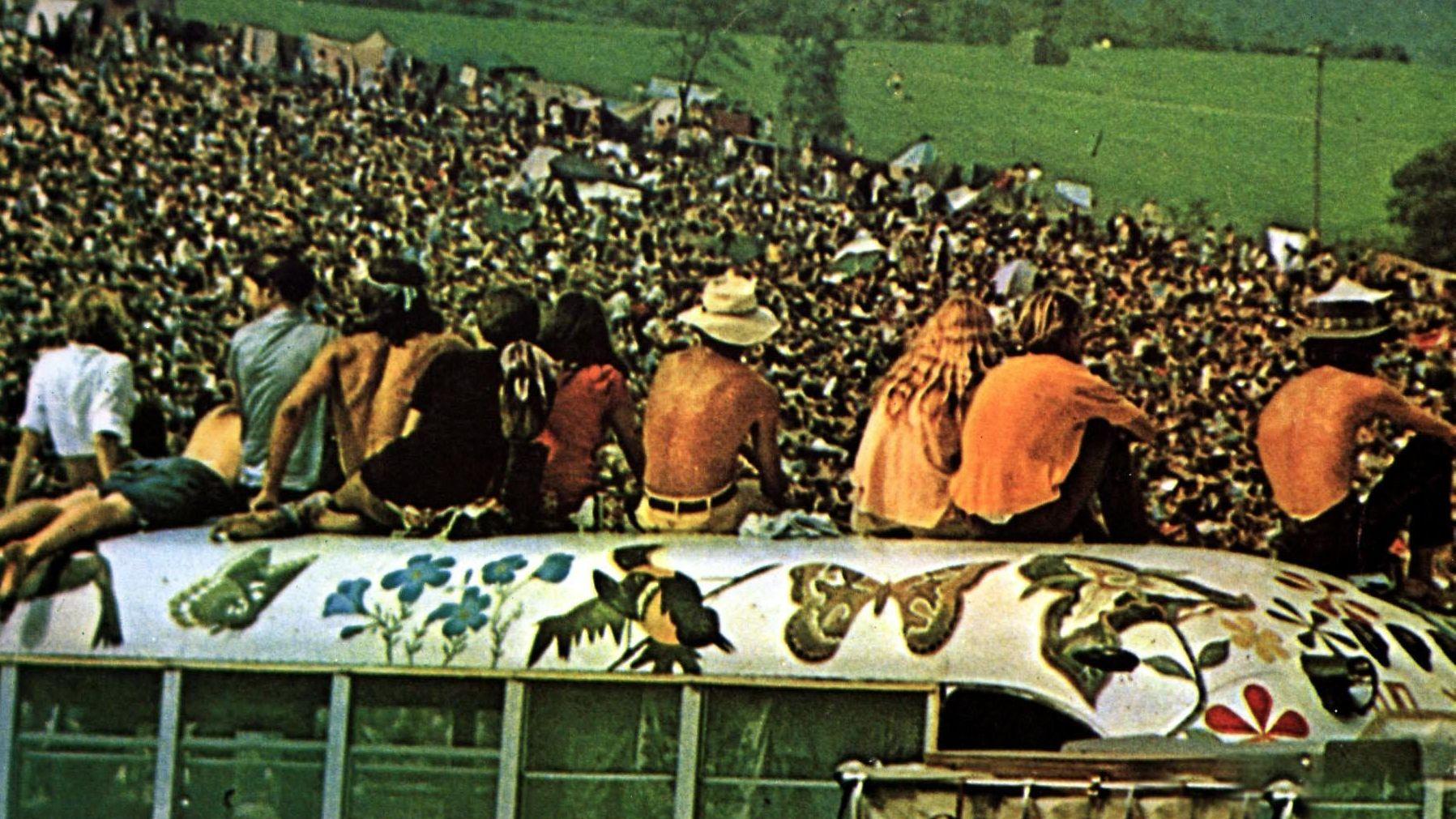 Woodstock: Festivalbesucher sitzen auf dem bemalten Dach eines Busses