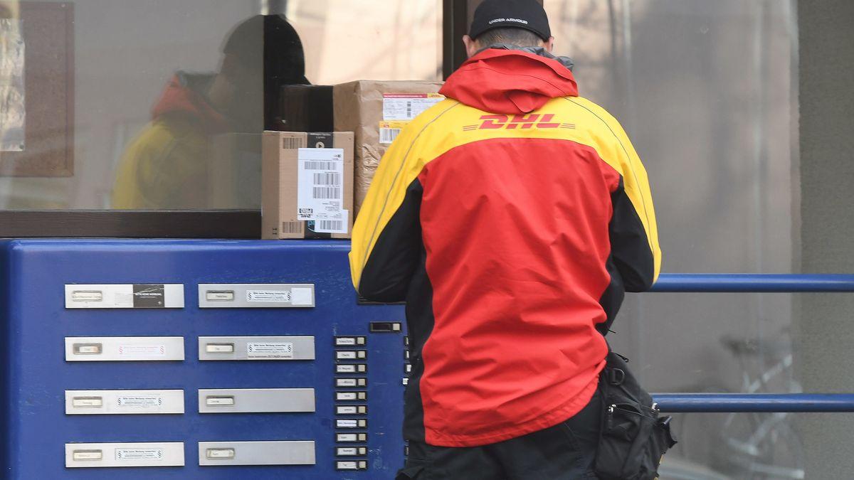Paketbote von DHL steht vor verschlossener Haustür