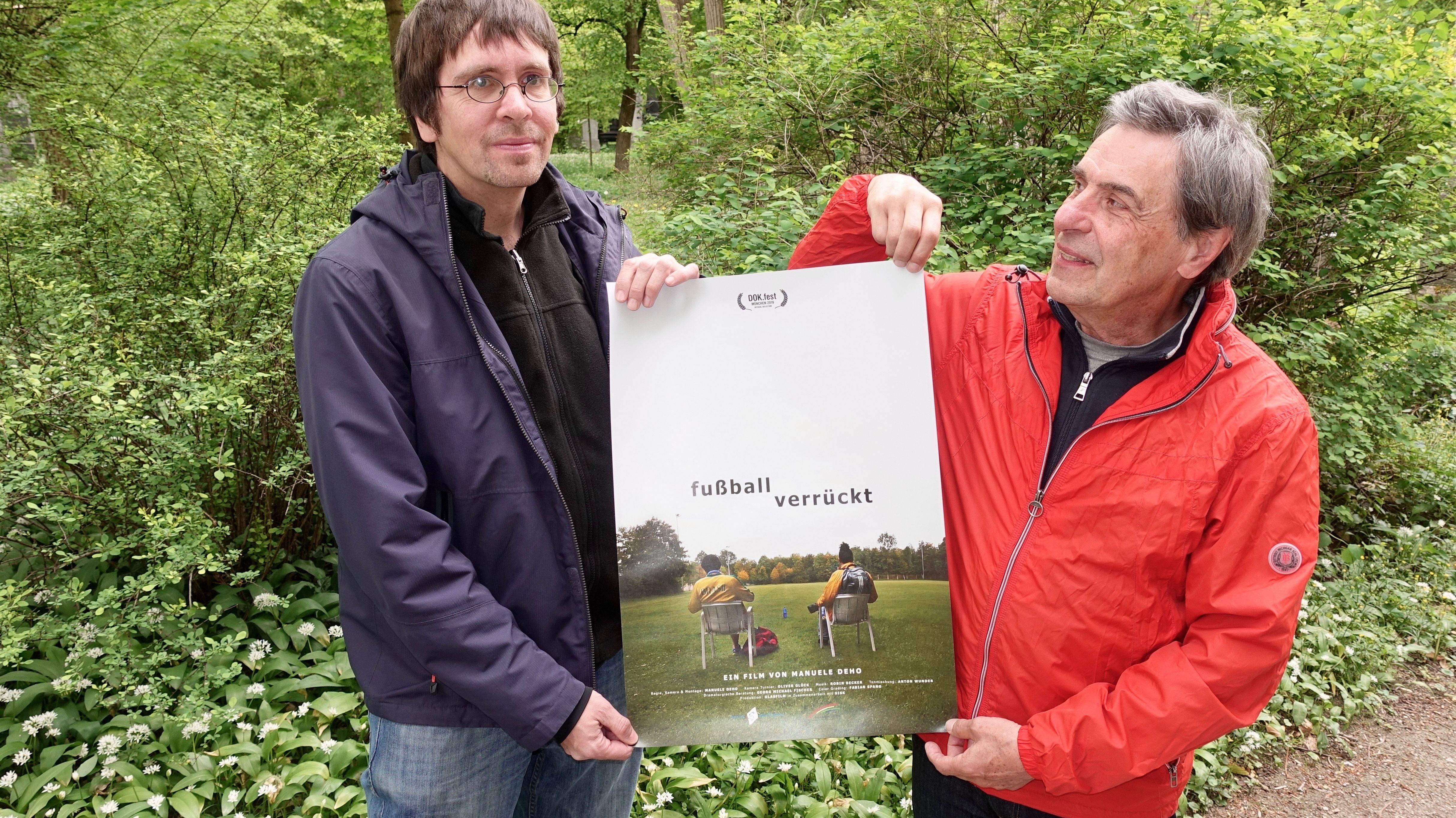 """Die Spieler Andreas Jahnke (links) und Manfred Bauer (rechts) mit dem Filmplakat von """"Fußballverrückt"""""""