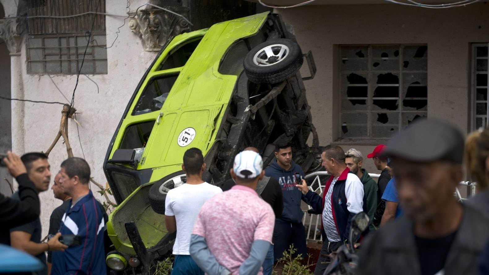 28.01.2017, Kuba, Havanna: Menschen stehen vor einem umgeworfenen Transporter, der an einer Hauswand liegt.