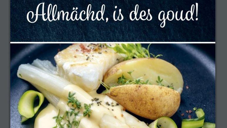 """Spargel mit Fisch, heller Soße, Kartoffel und Kresse auf einem schwarzen Teller, darüber der Titel in Schreibschrift """"Allmächd, is des goud!"""""""
