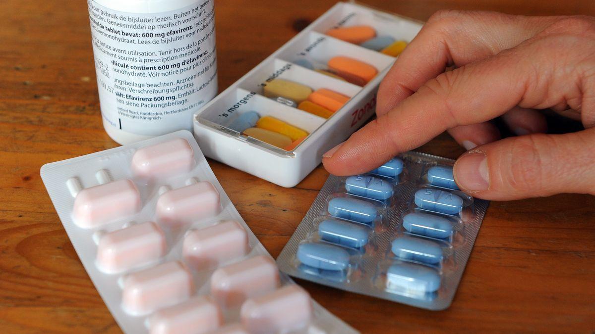 Tabletten eines an Aids erkrankten Menschen liegen in Tagesrationen und in Blistern sowie einer Dose auf einem Tisch.