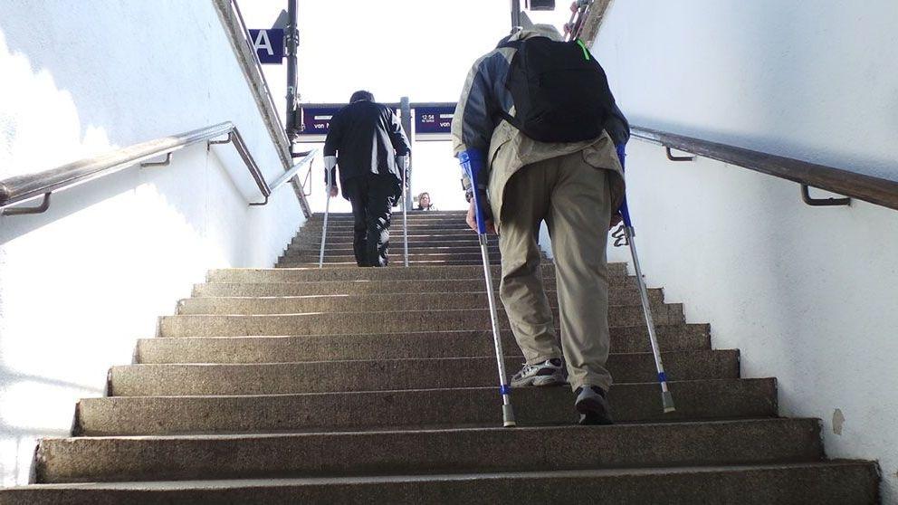 Zwei Senioren mit Krücken steigen eine Treppe am Fürther Hauptbahnhof empor.