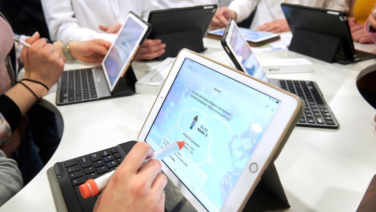 Menschen arbeiten an einem Tablet.