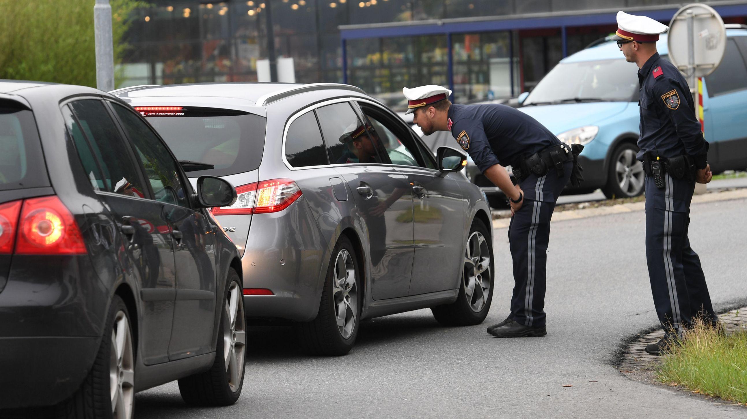 Österreichische Polizisten kontrollieren Fahrzeuge auf einer Bundesstraße in Tirol