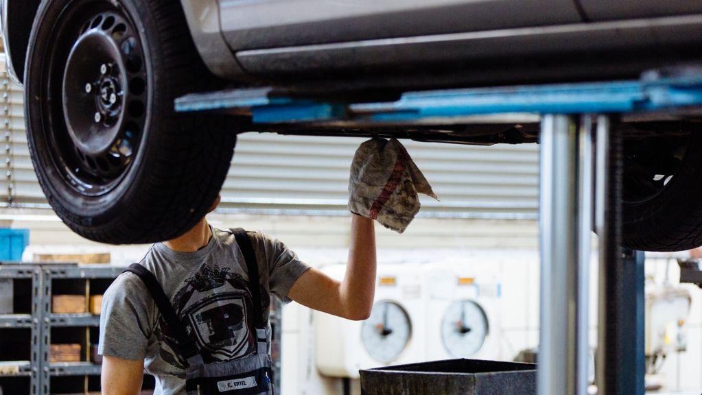 Ein Mitarbeiter arbeitet in einer Autowerkstatt an einem Autoreifen.