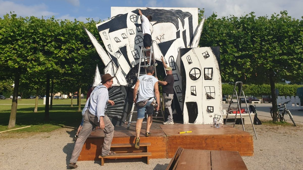 Für eine open air Bühne im Park bauen drei Männer auf einem Holzpodest schwarzweiß gemalten Kulissen von Häusern auf