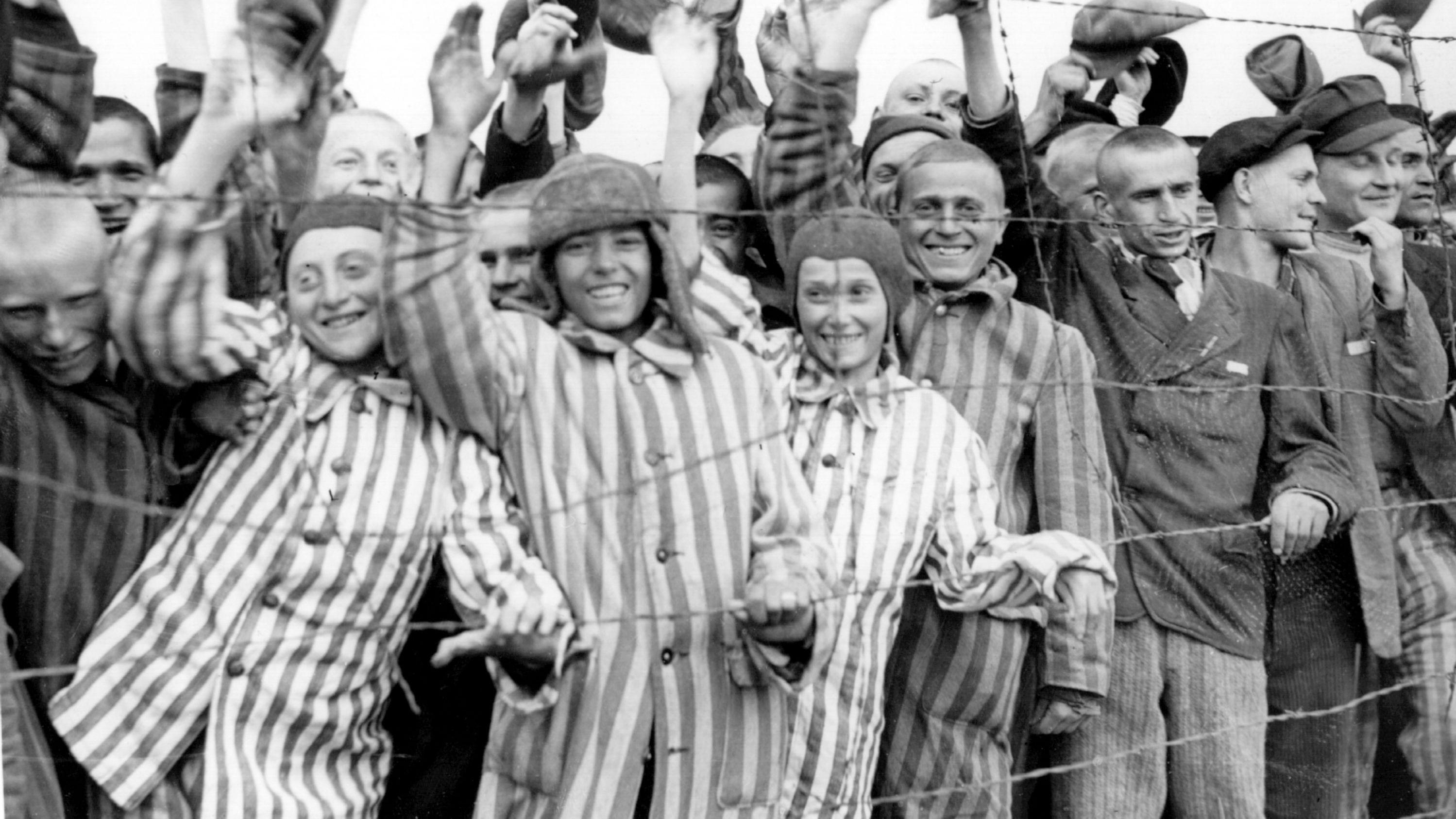 Historische Aufnahme einer Gruppe von KZ-Häftlingen hinter Stacheldraht, die nach der Befreiung des Lagers winken