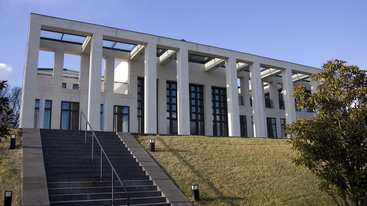 Strenge Betonsäulen und dahinter ein mächtiger Bau mit Glasgittern und großen Fenstern: Erweiterungsbau der Deutschen Botschaft in Washington von Oswald Mathias Ungers