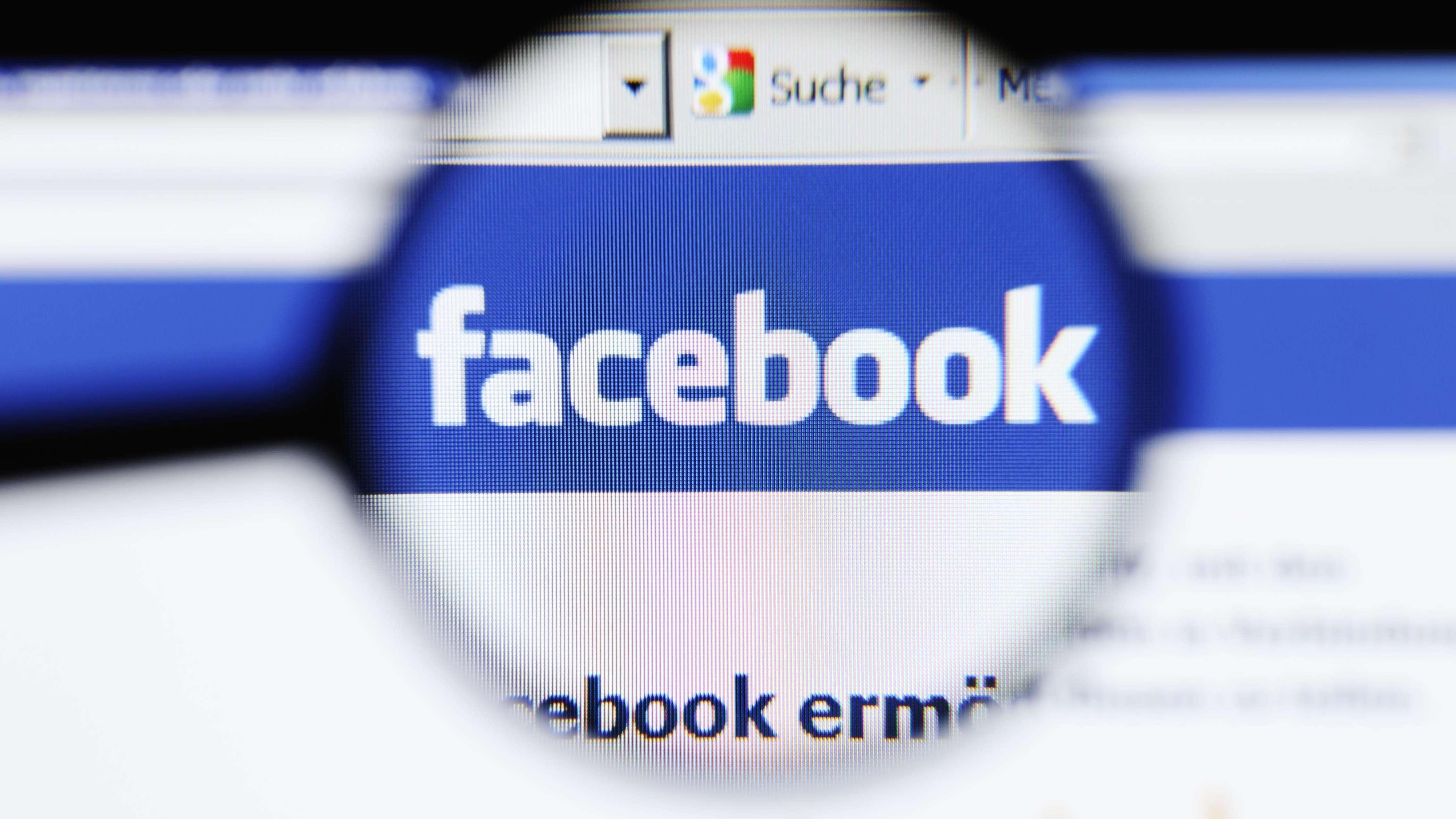 Facebook-Logo unter einer Lupe