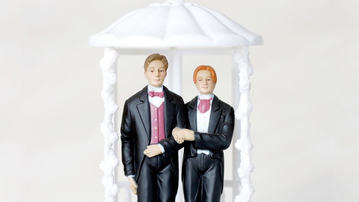Zwei männliche Plastikfigürchen Arm in Arm