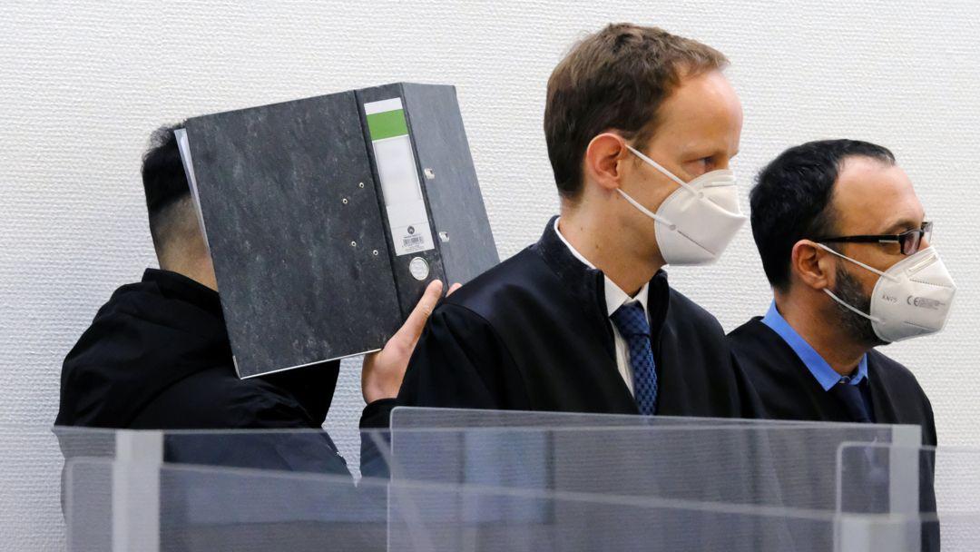 Ein Angeklagter verbirgt im Sitzungssaal des Landgerichts Ingolstadt sein Gesicht hinter einem Aktenordner. Davor stehen seine Verteidiger Andreas Ruch und Adam Ahmed (r).