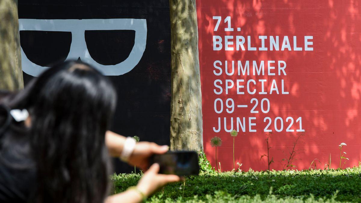 """Eine Passantin fotografiert auf der Museumsinsel ein Plakat mit der Aufschrift """"71. Berlinale Summer Special 9-20 June 2021"""". Dort laufen aktuell die Vorbereitungen für die geplanten Open Air Filmvorführungen."""
