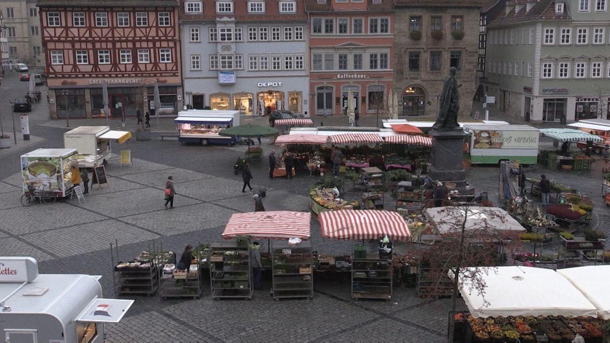 Blick auf den Coburger Markt mit seinen Ständen, die mit weißen oder roten-weißen Planen überdacht sind.