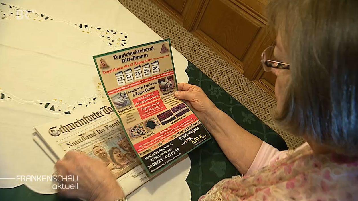 Ortrun Hensel schaut sich die Werbung der betrügerischen Teppichreiniger aus der Zeitung an.