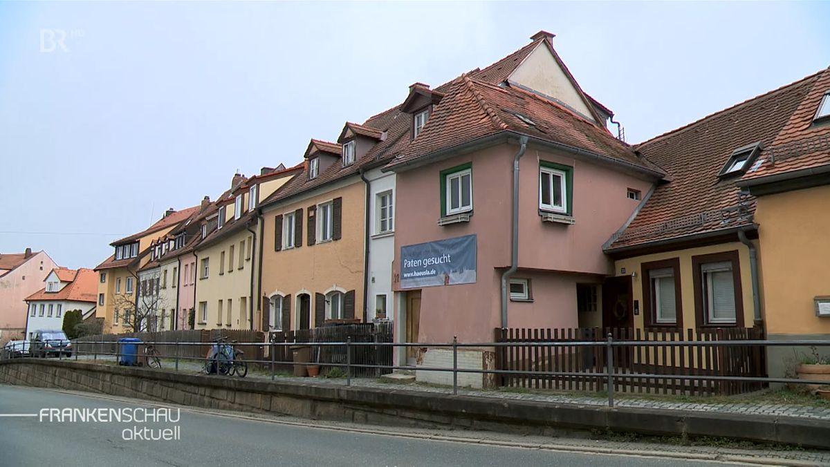 """""""Paten gesucht"""" steht auf einem Transparent, das an der Fassade des kleinsten Bamberger Wohnhauses hängterg"""