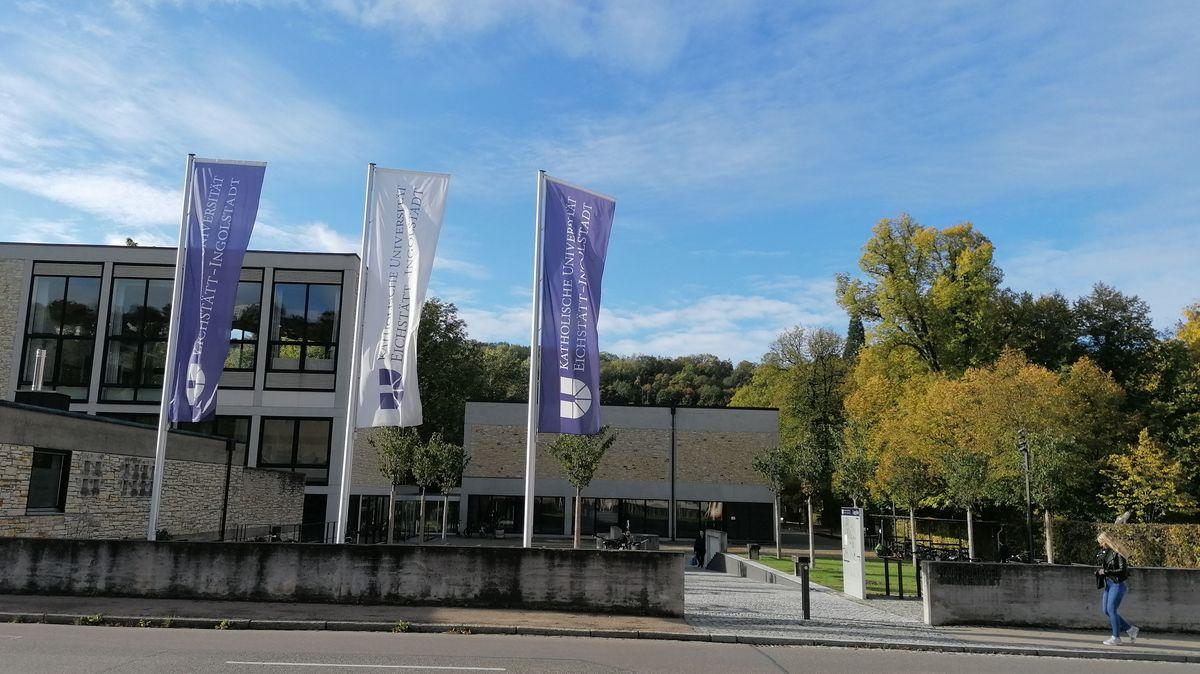 Katholische Universität Eichstätt-Ingolstadt, moderner Betonbau mit Glasfenstern und Fahnen im Vordergrund