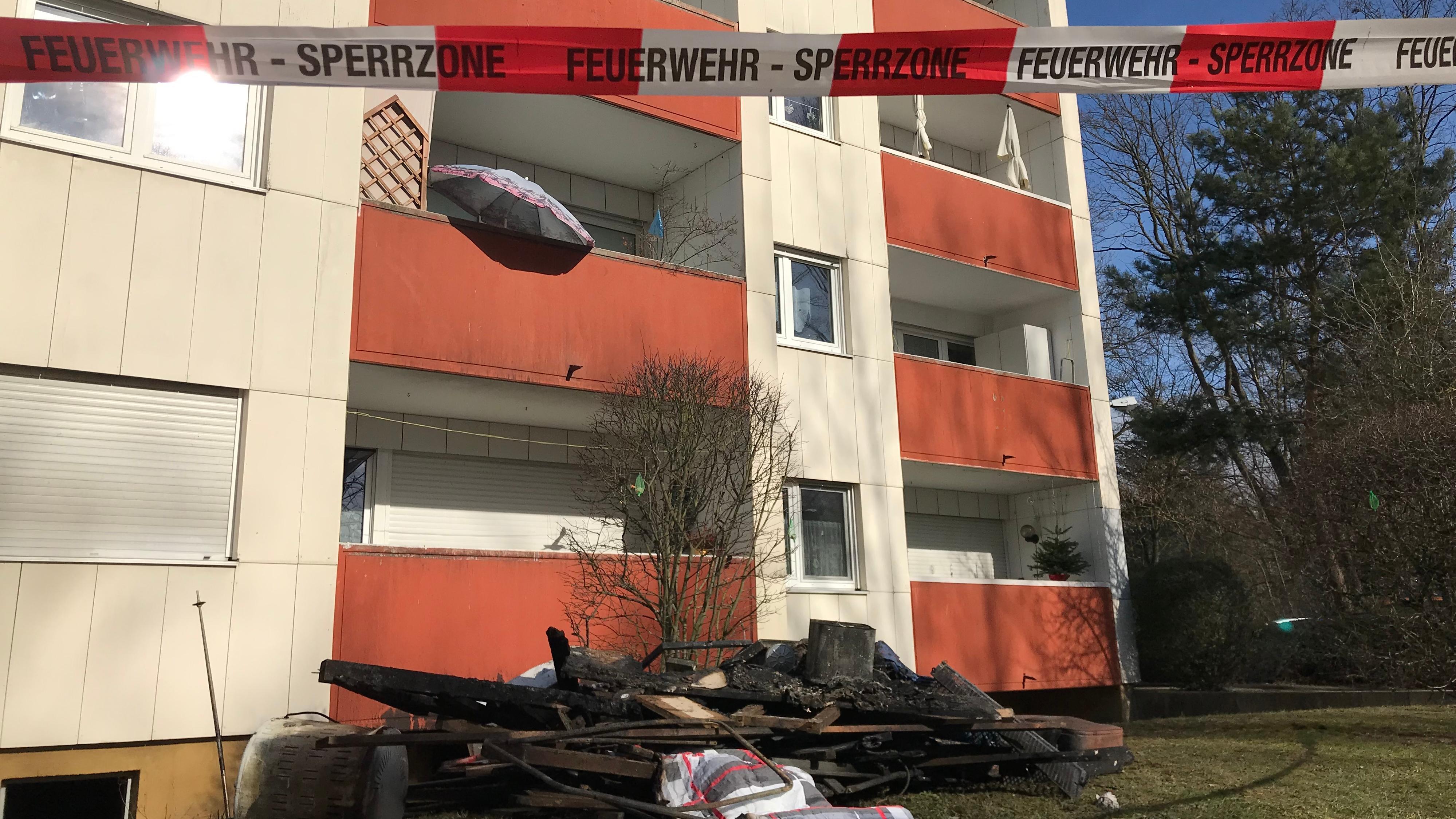 Verbrannter Schutt liegt auf der Wiese vor einem Mehrfamilienhaus.