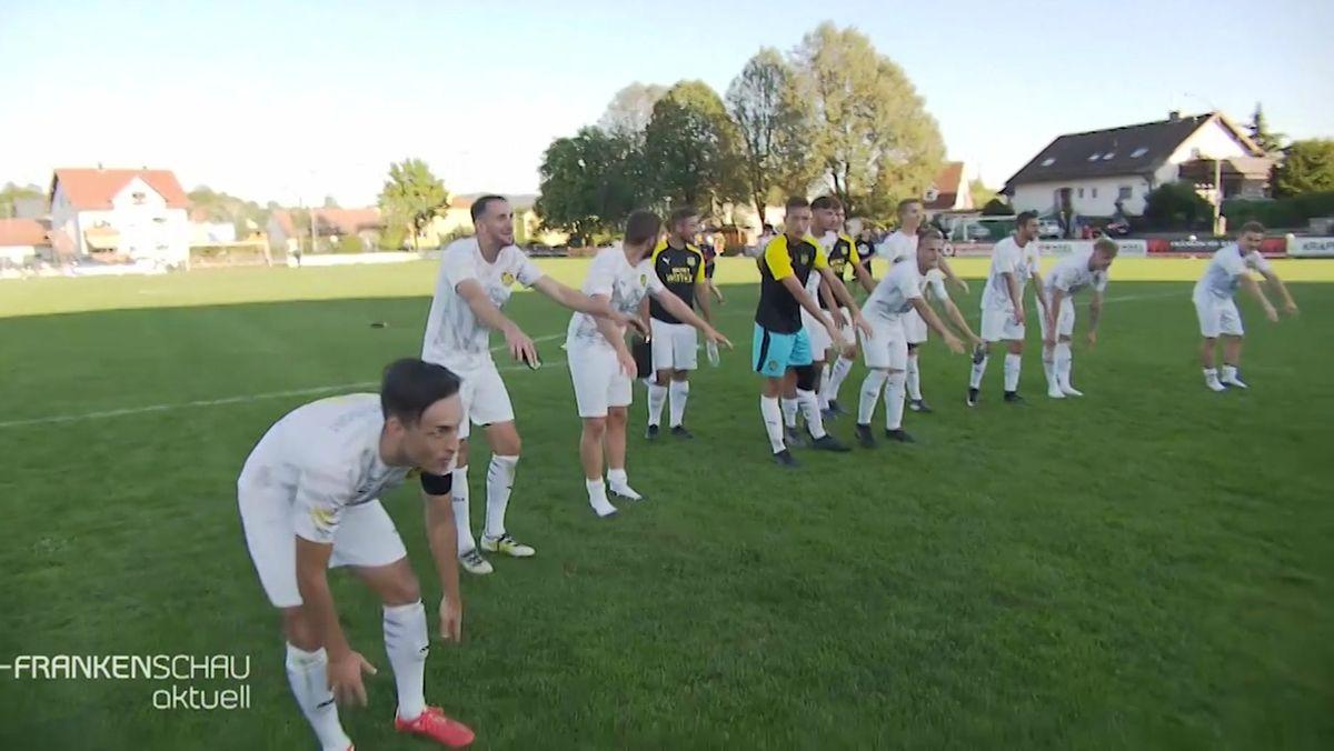 Fußballer des SV Merkendorf machen auf dem Spielfeld die La-Ola-Welle.