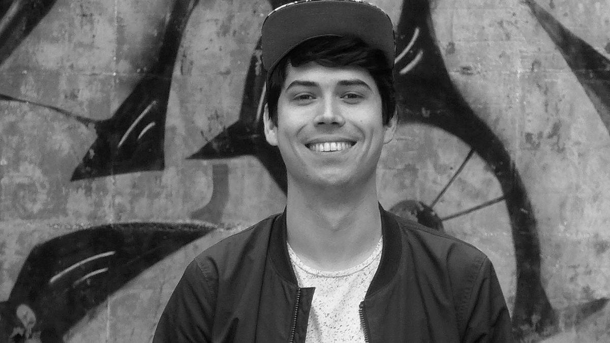 Lyriker Tristan Marquardt blickt, vor einer besprühten Wand stehend, lächelnd in die Kamera