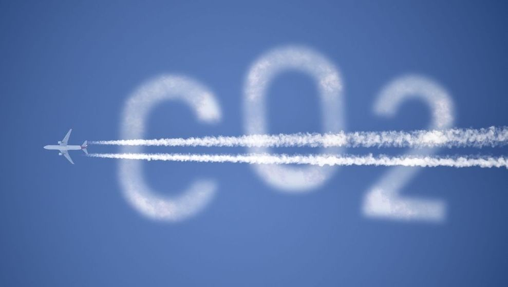 Flugzeug mit Kondensstreifen und Schriftzug CO2
